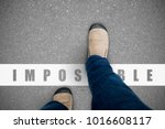 Small photo of One wearing jeans and brown suede shoes walking over the impossible line representing positive can do and everything possible concept.