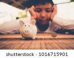 young asian boy saving money...   Shutterstock . vector #1016715901