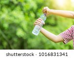 hand holding a bottle of water... | Shutterstock . vector #1016831341
