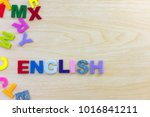 Small photo of Colorful english alphabet sponge on wooden table background. ABC,Cube foam english letters on wood desk background. Learn english concept. top view.