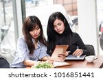 two asian woman using tablet... | Shutterstock . vector #1016851441