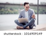 attractive man sitting outside... | Shutterstock . vector #1016909149