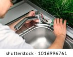Plumber Repairing The Faucet O...