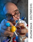 Small photo of Crazy scientist with model molecules building a new chemical compound