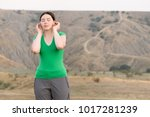 Small photo of The girl tourist standing and doing acupressure ears with closed eyes on the background of mountainous steppe, behind the sun is shining