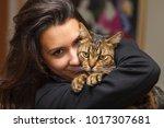 Stock photo pretty girl loving her pet tabby cat 1017307681