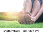 Small photo of Foot Pain Leg of beauty woman sitting on the road park holding her feet and stretch the muscles in morning sunlight .Health care and spa concept.