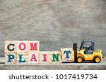 Stock photo toy forklift hold letter block t to complete word complaint on wood background 1017419734