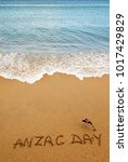 Small photo of Words Anzac day and Australian flag on the sand of seashore.Lest we forget