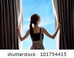 Young Woman Opening Curtains...