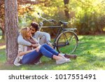 young couple in love sitting in ... | Shutterstock . vector #1017551491
