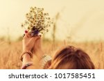 girl holding flowers in a wheat ... | Shutterstock . vector #1017585451