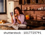 the girl drinks coffee with a... | Shutterstock . vector #1017725791