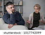Small photo of Upset man refusing to listen to his constantly complaining wife