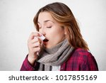 Small photo of Sideways portrait of young woman has allergic rhinitis, sneezes into napkin, has headache, wears scarf on neck, isolated over white background. Sickness, seasoanl virus and health problem concept