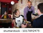 polite waiter bringing ordered... | Shutterstock . vector #1017892975