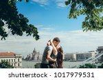 Small photo of Young happy attractive couple in love is almost kissing and hugging at the background of the magnificent landscape view of Budapest, Hungary.