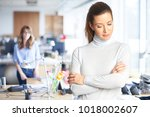 Stock photo shy businesswoman wearing casual clothes while standing at the office with arms crossed 1018002607