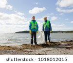 boys in safety vests cleaning... | Shutterstock . vector #1018012015