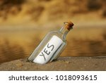 Small photo of Bottle on the beach with an affirmative answer inside, yes, positive message