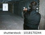 rear view of man aiming gun at... | Shutterstock . vector #1018170244