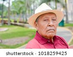sad old latin man wearing hat... | Shutterstock . vector #1018259425