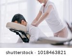 masseuse doing seated back... | Shutterstock . vector #1018463821