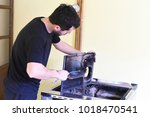 man cleaning wood burning stove.... | Shutterstock . vector #1018470541
