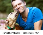 Stock photo guy with his dog hugging in the park 1018533754