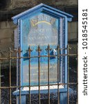 Small photo of WREXHAM, UK - FEBRUARY 01, 2015: Blue and yellow sign outside an abandoned church in Wales. The paint on the Welsh language sign and iron railings is weathered with neglect and is peppered with snow.