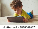 cute little boy using a pad.... | Shutterstock . vector #1018547617