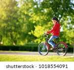 child on a bicycle at asphalt... | Shutterstock . vector #1018554091