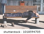 poor homeless man with shoes on ... | Shutterstock . vector #1018594705