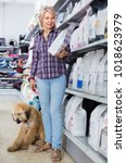 Small photo of female customer with Afghan Shepherd puppy choose pet food in zoo store