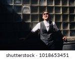 the handsome groom stands near... | Shutterstock . vector #1018653451