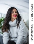 Small photo of Woman smiling with perfect smile and white teeth in a livingroom and looking at camera