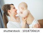 mother hugs baby toddler... | Shutterstock . vector #1018730614