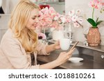 Small photo of Attractive cheerful mature woman having cup of coffee relaxing at hime smiling cheerfully using her smart phone apartment indoors house comfort technology mobility carrier social media maturity