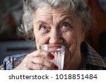 elderly woman drinks water   Shutterstock . vector #1018851484