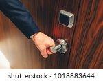 man in a suit opens the door to ... | Shutterstock . vector #1018883644