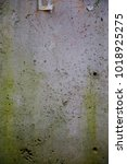 Small photo of The vertical texture of old industrial concrete wall with rude green spots and holes