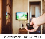 a tv remote in the person's... | Shutterstock . vector #1018929511