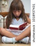 cute little girl reading book | Shutterstock . vector #1018937431
