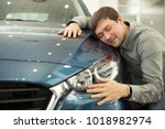 Stock photo portrait of a mature man smiling joyfully embracing a new car at the dealership showroom copyspace 1018982974