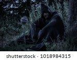 hooded man wearing a cloak in a ... | Shutterstock . vector #1018984315