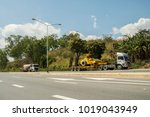 Small photo of Phetchabun, THAILAND – January 31, 2018 Lowboy semi-trailer carrying vibratory soil compactor and freight bulk cement tank semi-trailer transporting powder cement on the Asian highway