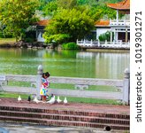 Small photo of Sanya, China - October, 20, 2017: Chinese girl on the shore of the lake near the Buddhist temple in China, Sanya