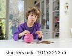 little boy putting coins into... | Shutterstock . vector #1019325355