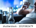 Small photo of Anynomous alcoholic taking sip of beer. Home full of empty bottles. Alcoholism and drinking problem concept. Man sipping alcohol late at night. Drunken sad guy sitting on sofa.
