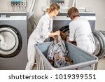 two washwomen taking of cleaned ... | Shutterstock . vector #1019399551